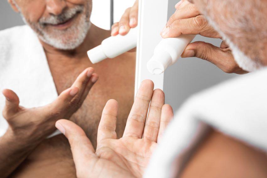 Hombre hidratando la piel del rostro